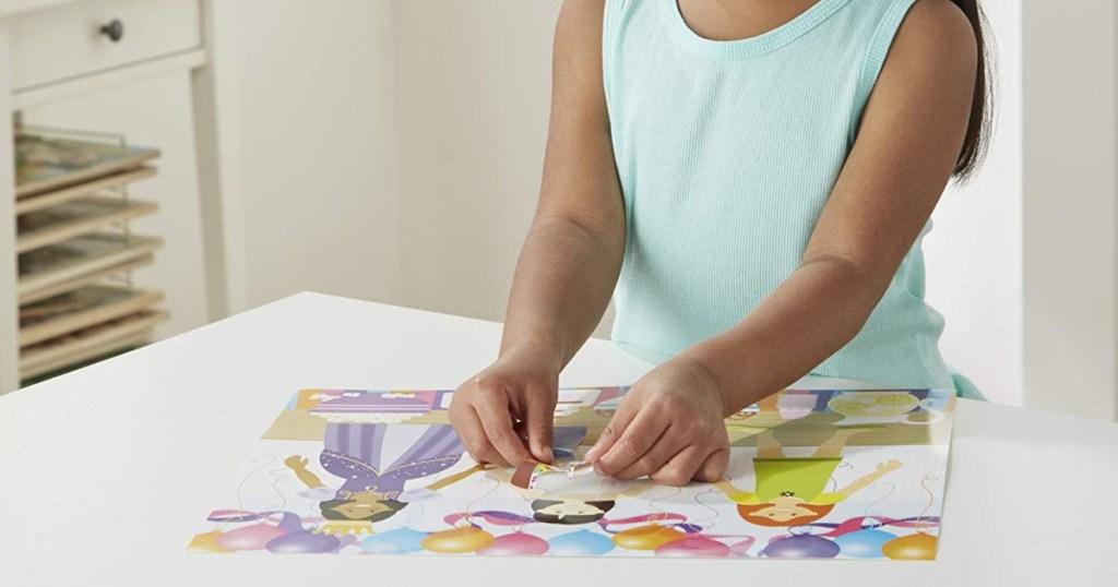 girl using melissa & doug sticker pad