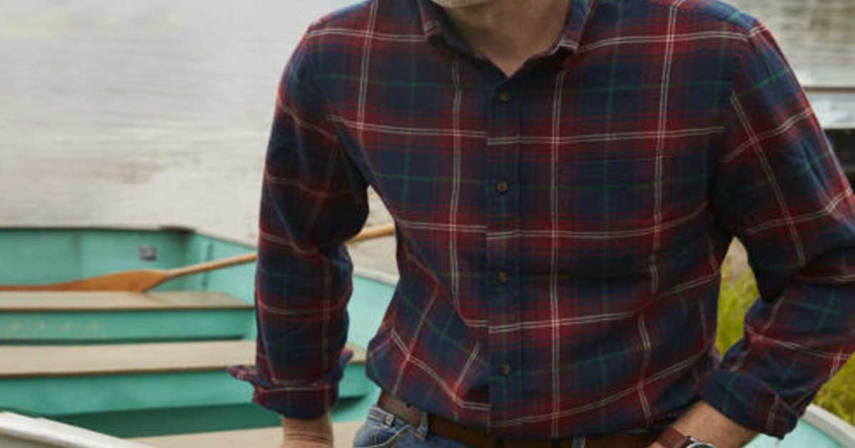 man sitting on a boat wearing a flannel shirt