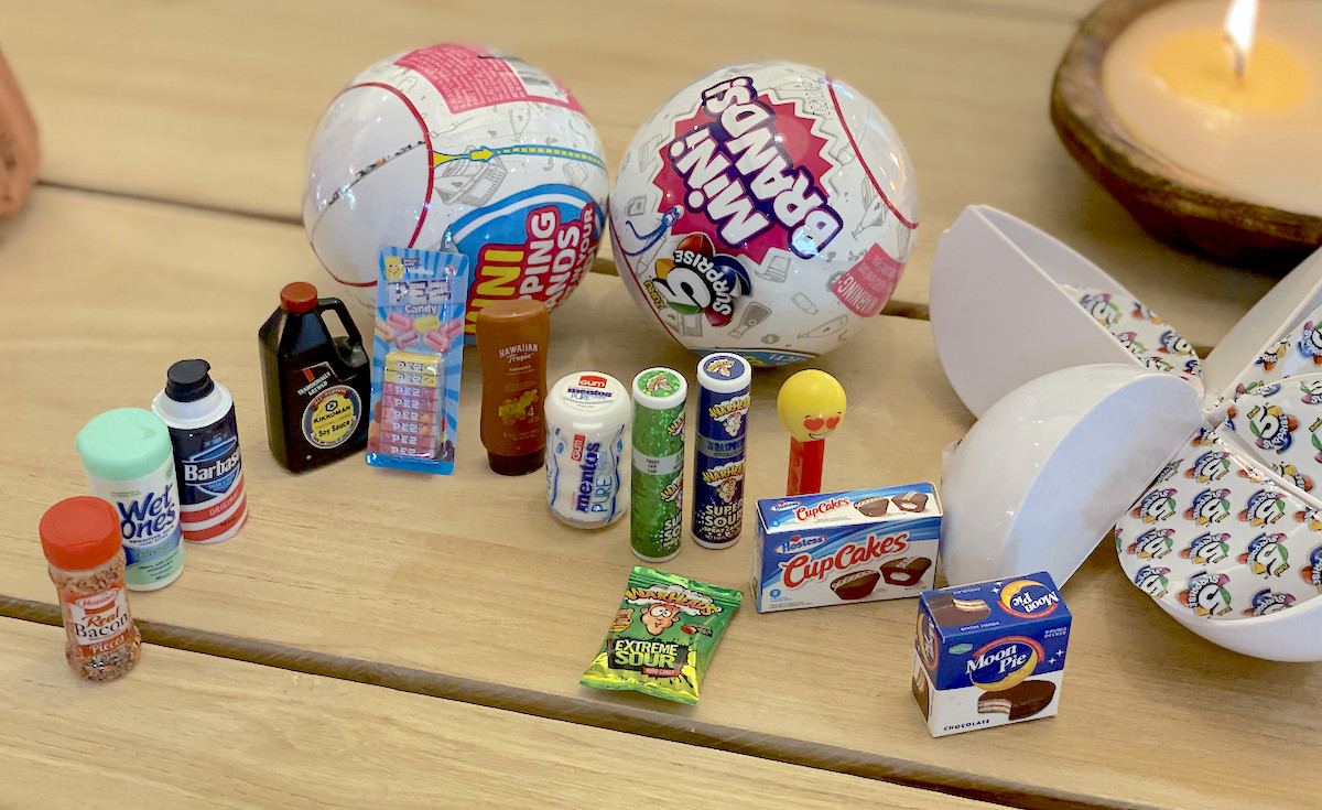 5 surprise mini brands balls on table with miniature food and personal care brands
