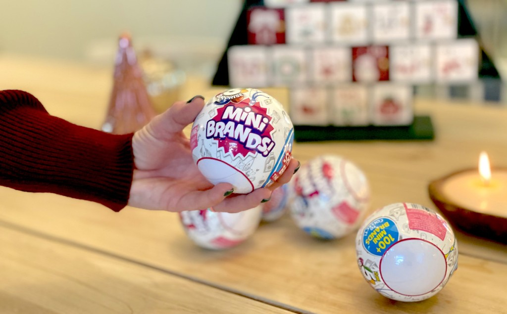 hand holding 5 surprise mini brands ball