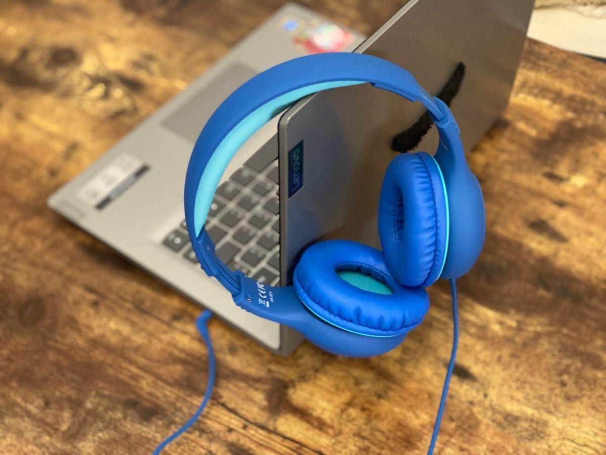 blue headphones hanging on side of laptop