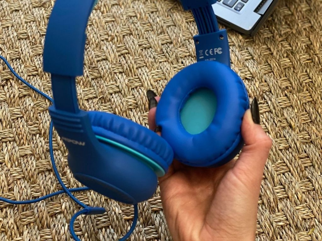 hand holding blue headphones