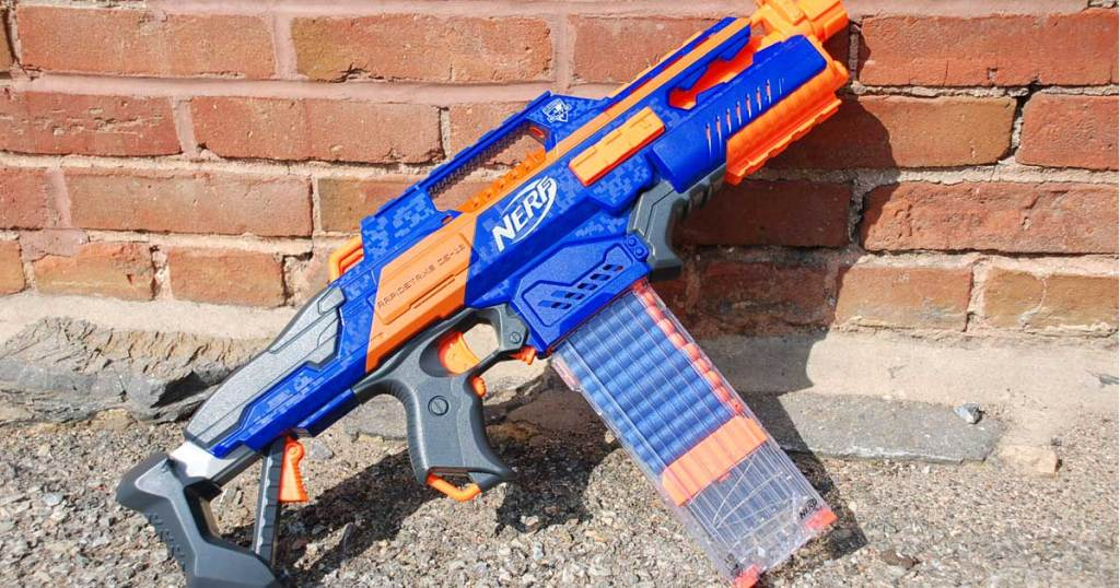 nerf gun on a gravel sidewalk next to a brick wall