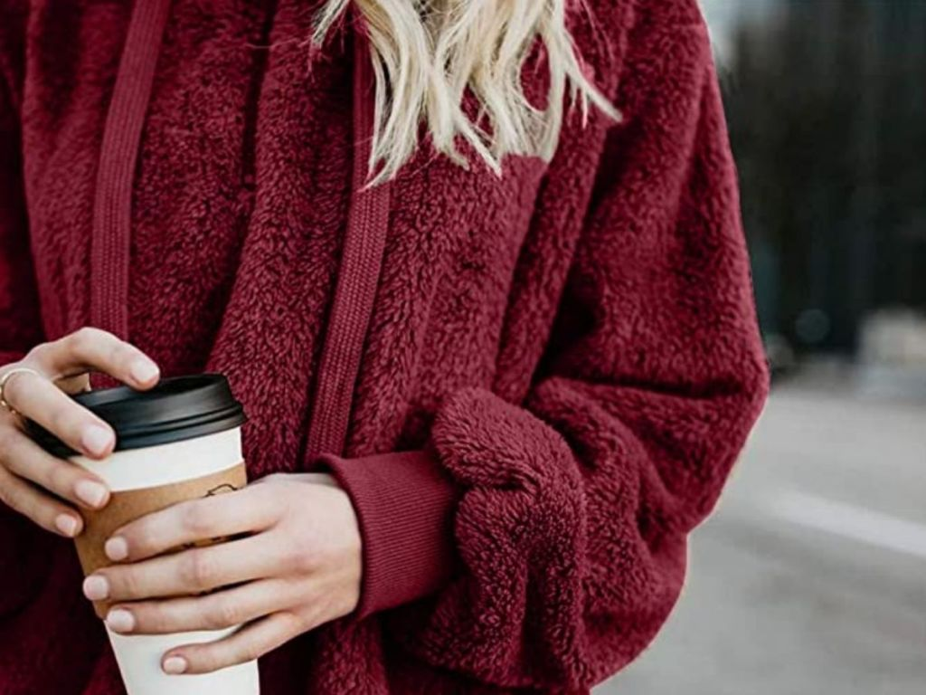 close up of woman wearing red sweatshirt holding coffee cup