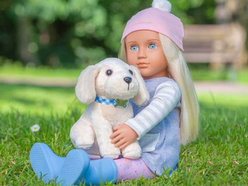 blonde doll with dog sitting in grass