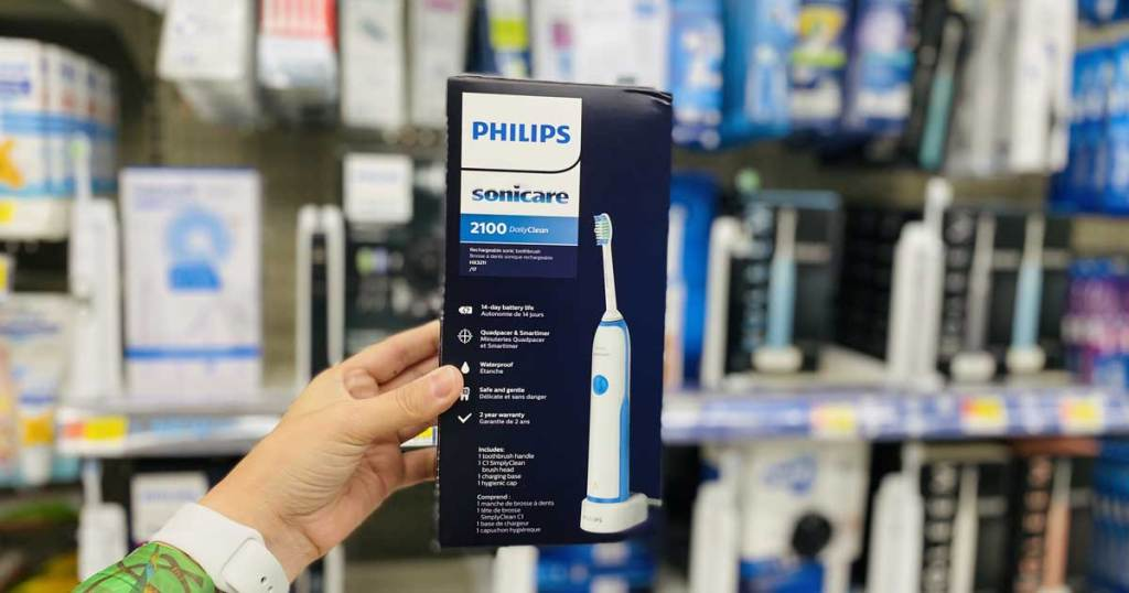 hand holding up an electric toothbrush in store