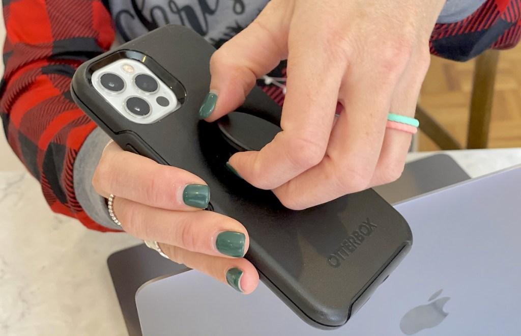 hand pulling up black popsocket off phone case