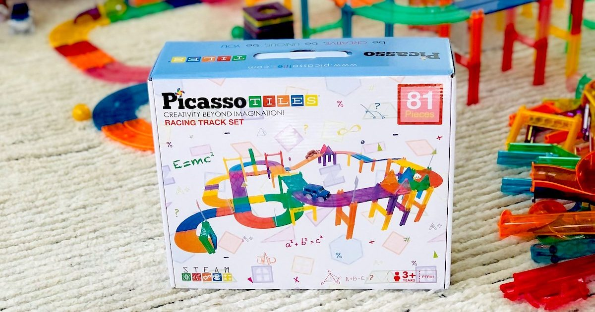 box of picasso tiles set sitting on carpet with race track behind it