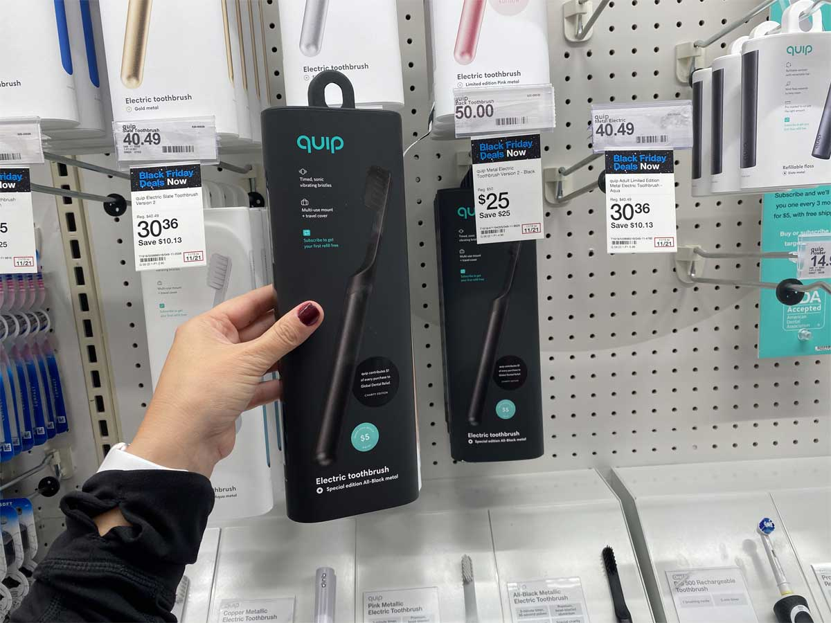 hand holding metal electronic toothbrush
