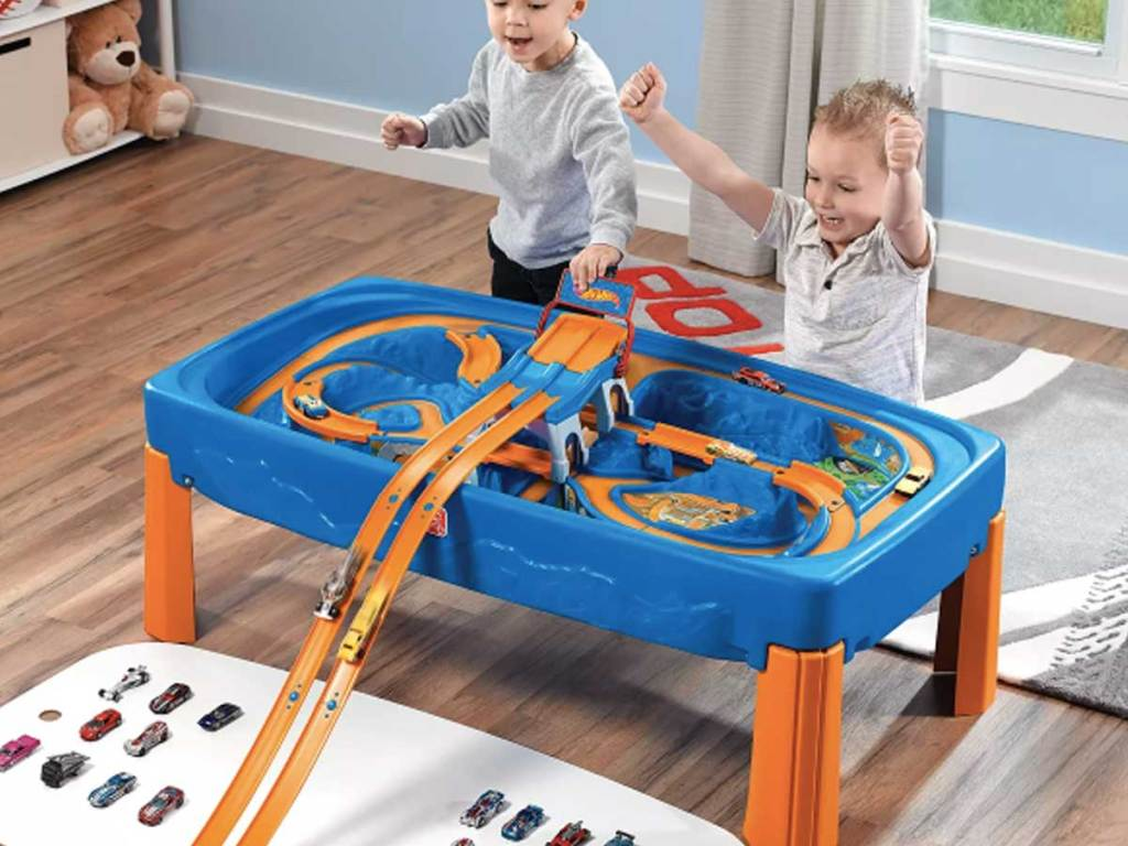 anak laki-laki bermain dengan mobil balap dan meja trek