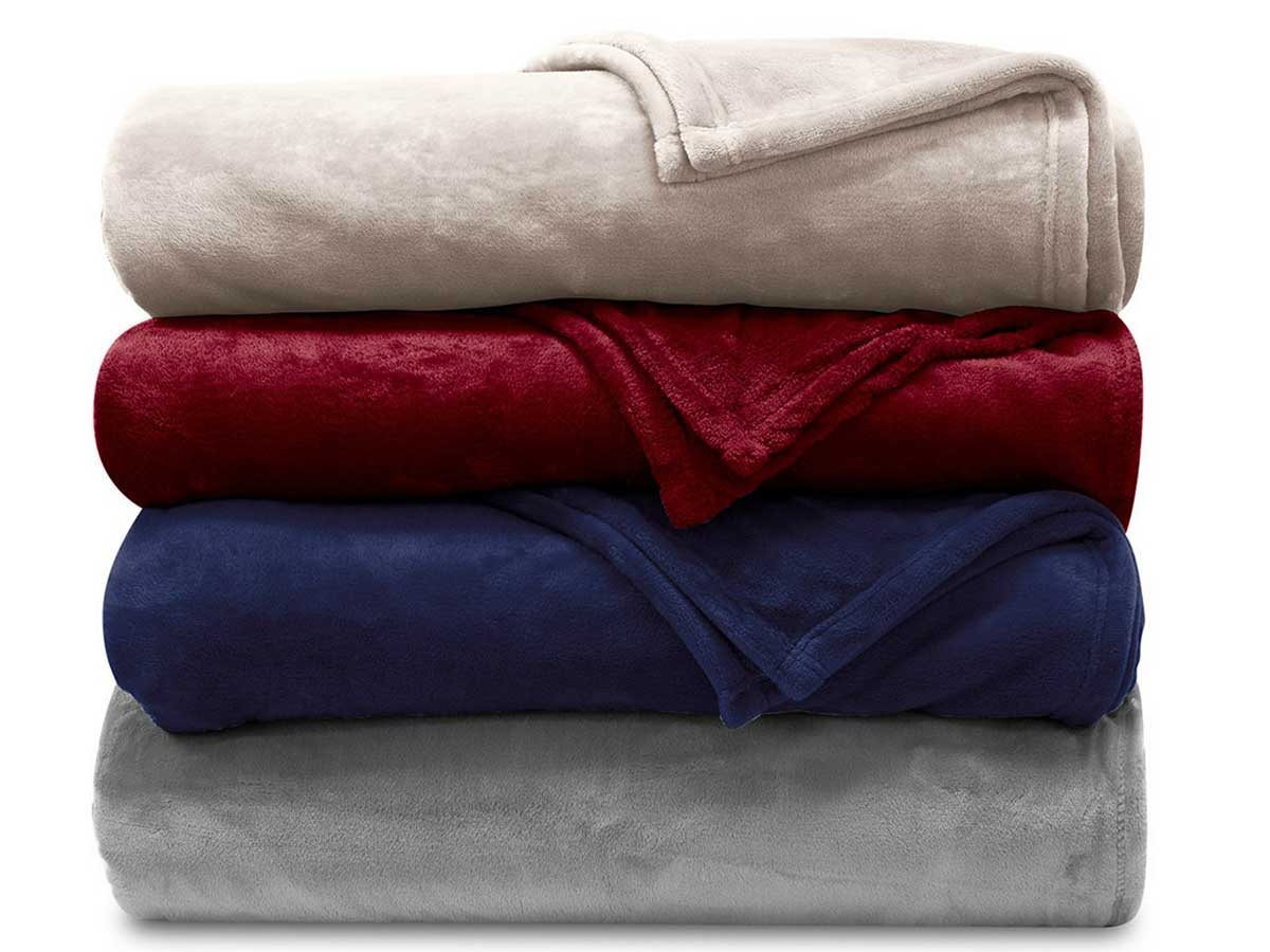 folded stack of blankets in four colors