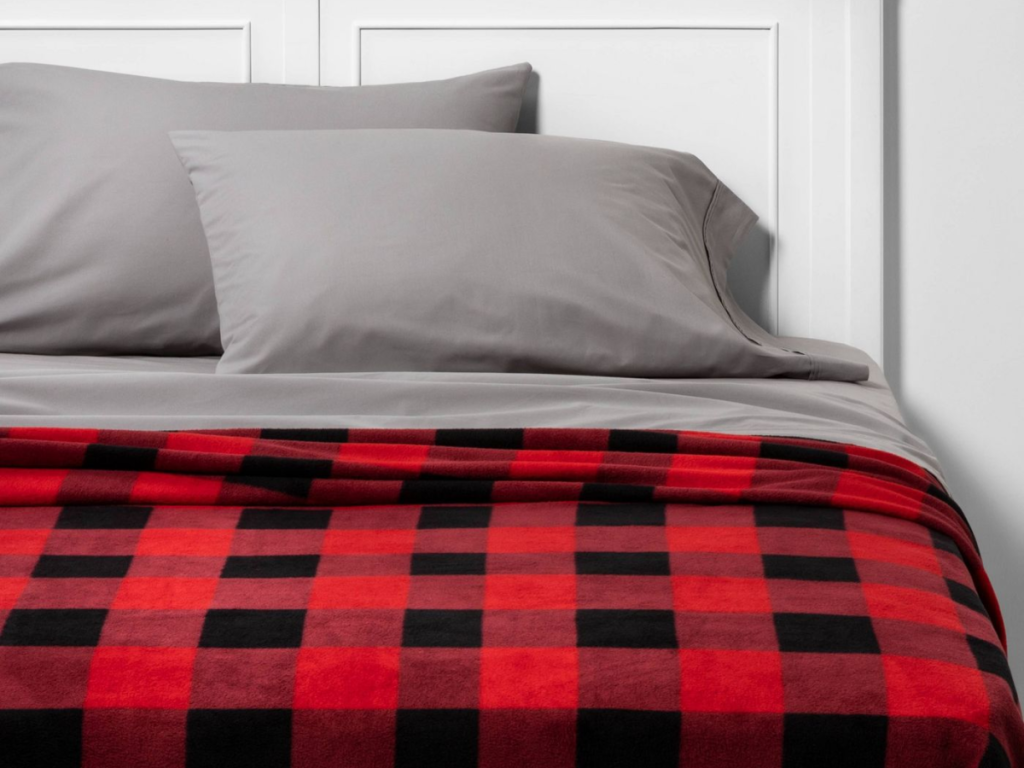 red and black checked blanket on a bed