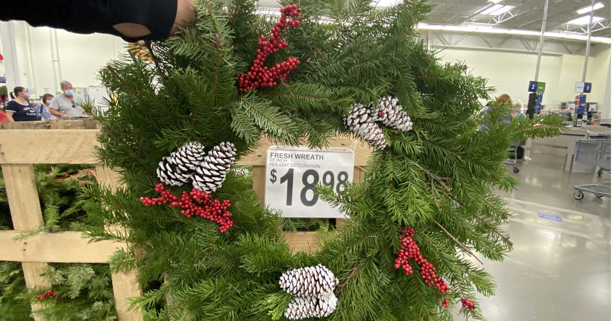 hand holding up a fresh evergreen wreath in sams club store