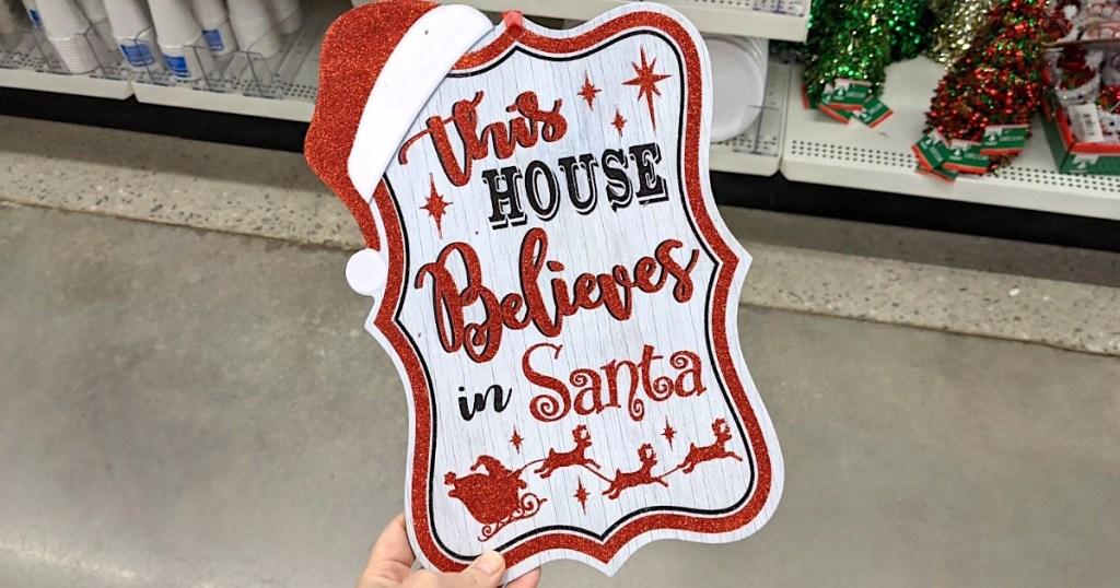 holding Santa sign