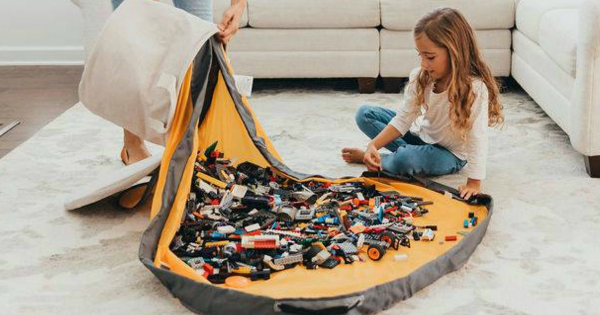 girl playing with LEGOs on a play mat