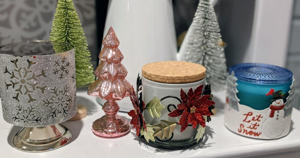 3 candles on white shelf with christmas decor