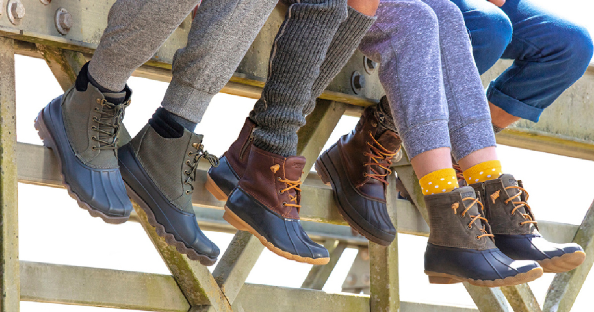 legs hanging down from fence with boots on