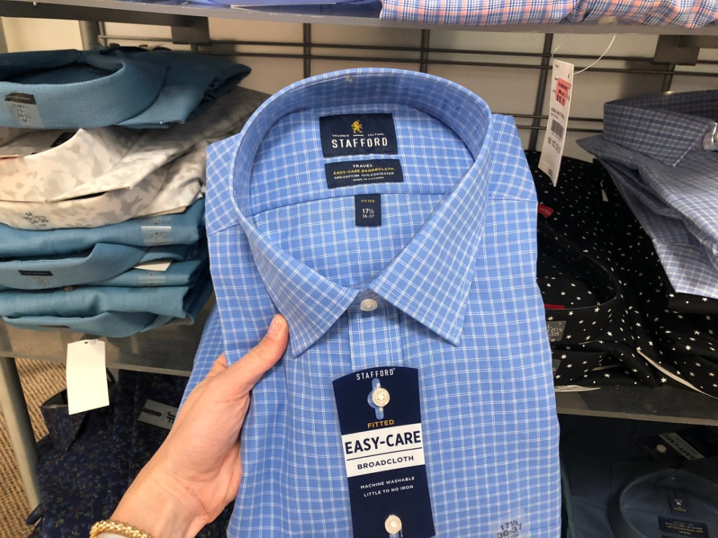 hand holding men's dress shirt in store
