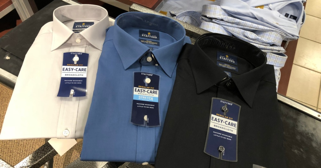3 men's button up shirts on table in store