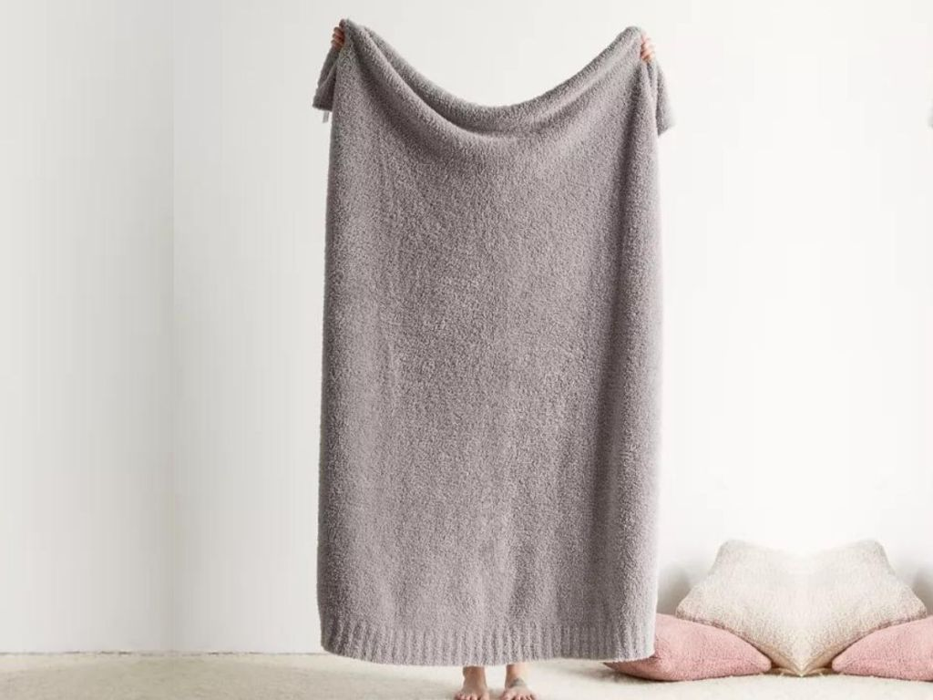 person holding up gray blanket