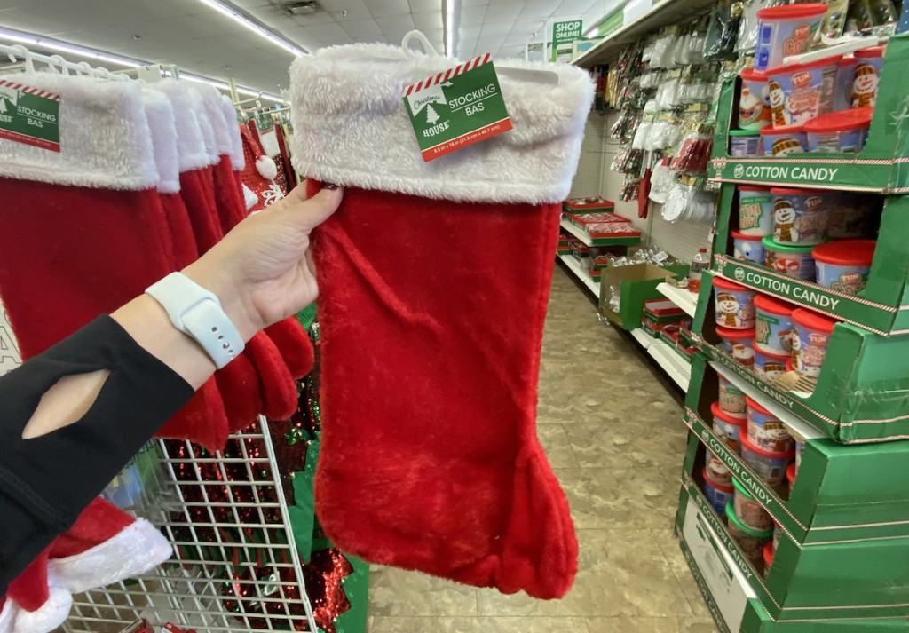hand holding red stocking in dollar tree christmas decoration aisle
