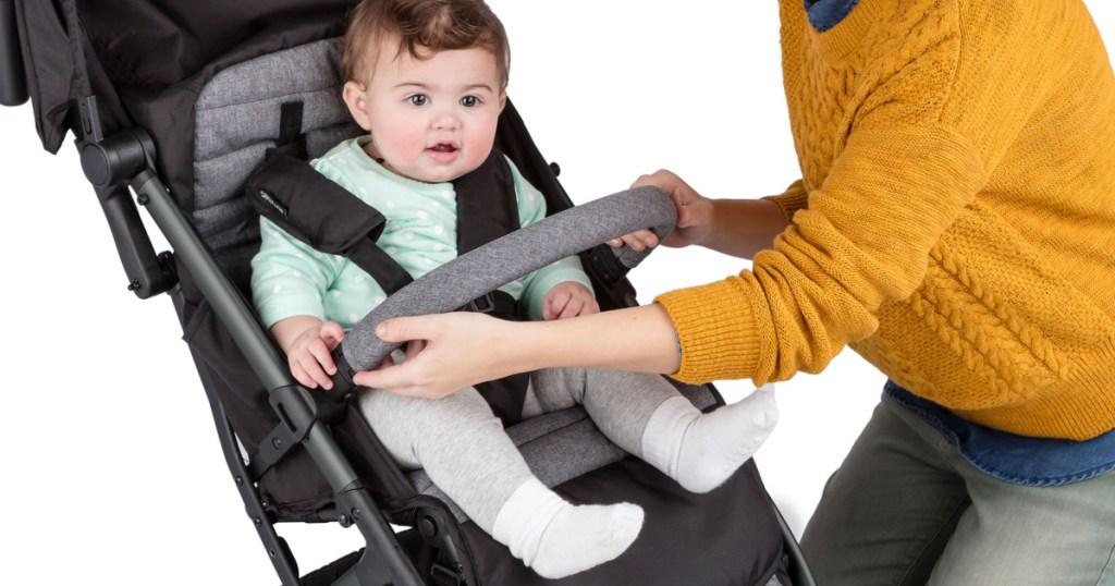 Wanita mengunci bayi ke dalam kereta dorong dengan latar belakang putih