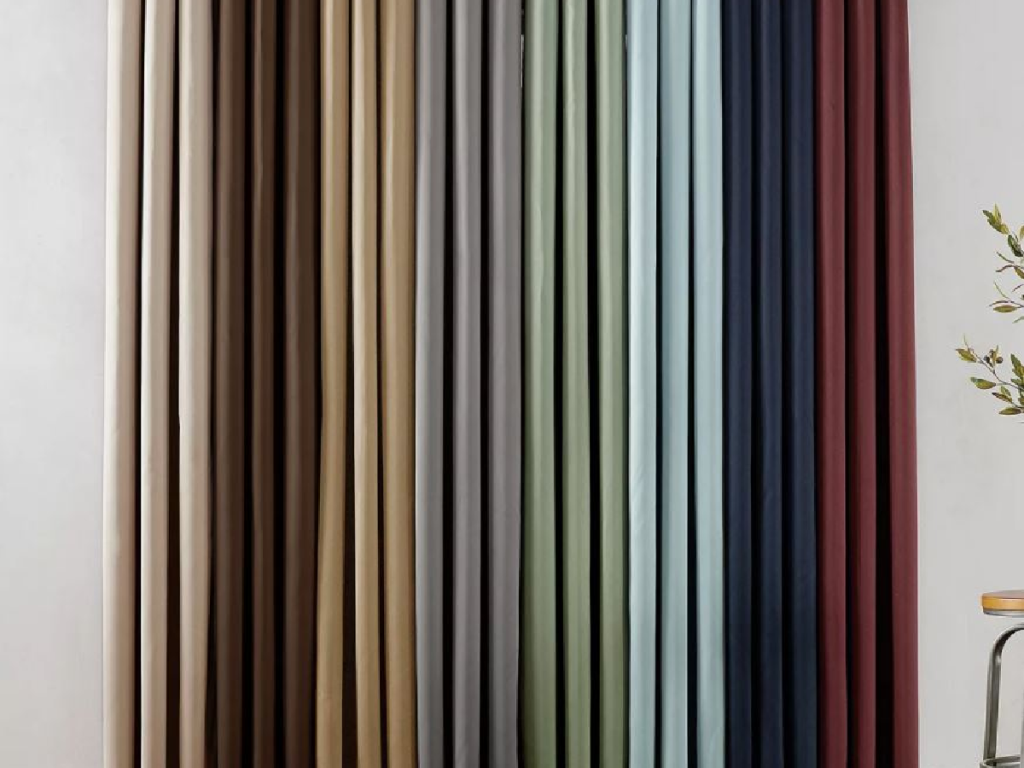 several colors of curtains hanging on rod