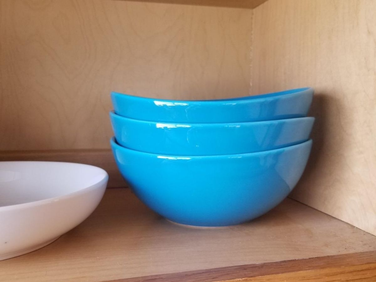 blue bowls stacked in cupboard