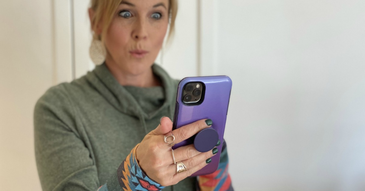 woman looking at her phone with a surprised face