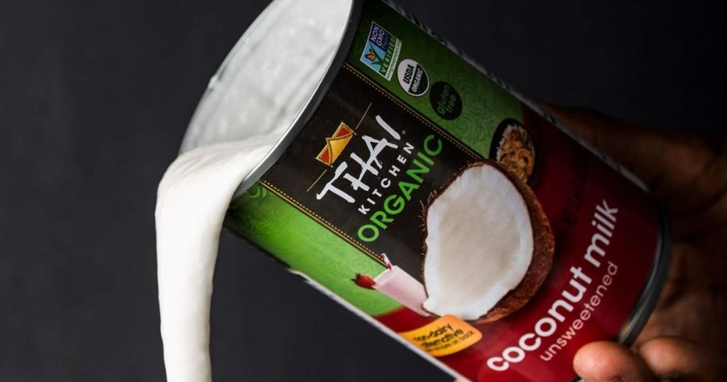 hand holding a can of coconut milk while pouring it out of the can