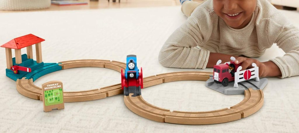 little boy playing with thomas and friends track