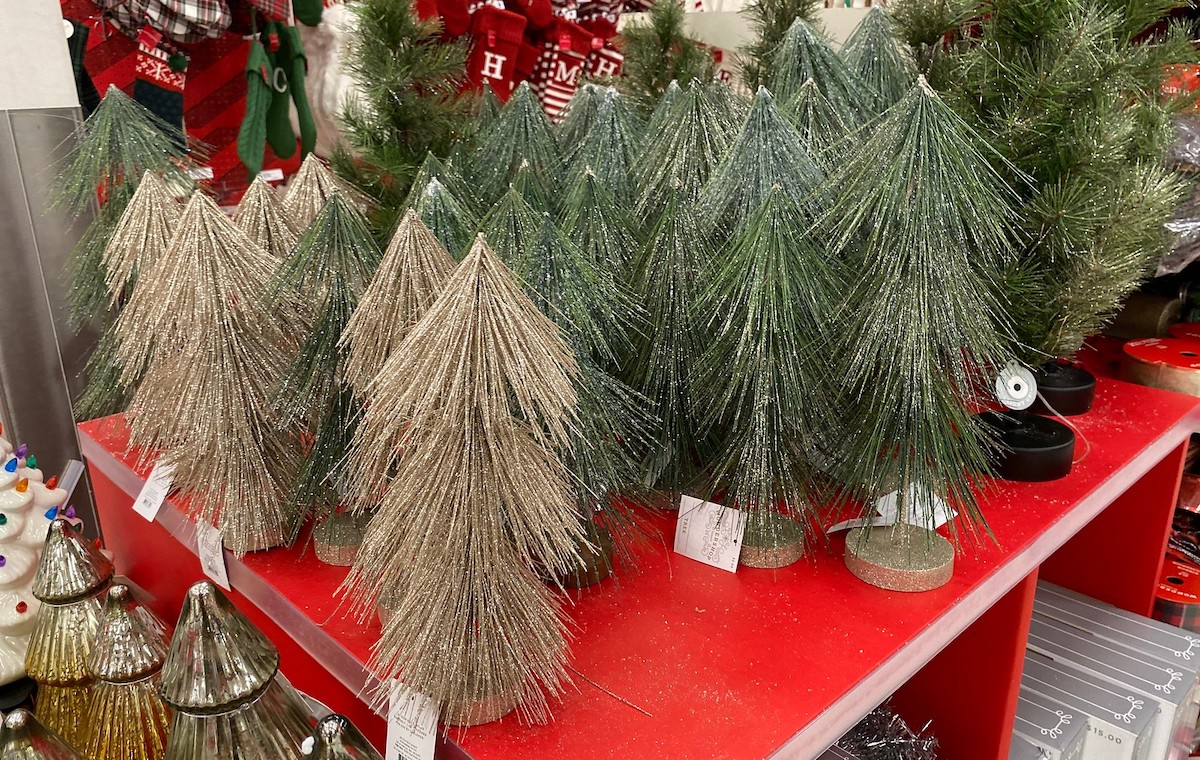 tons of target christmas decor gold and green christmas tinsel trees on red store table display