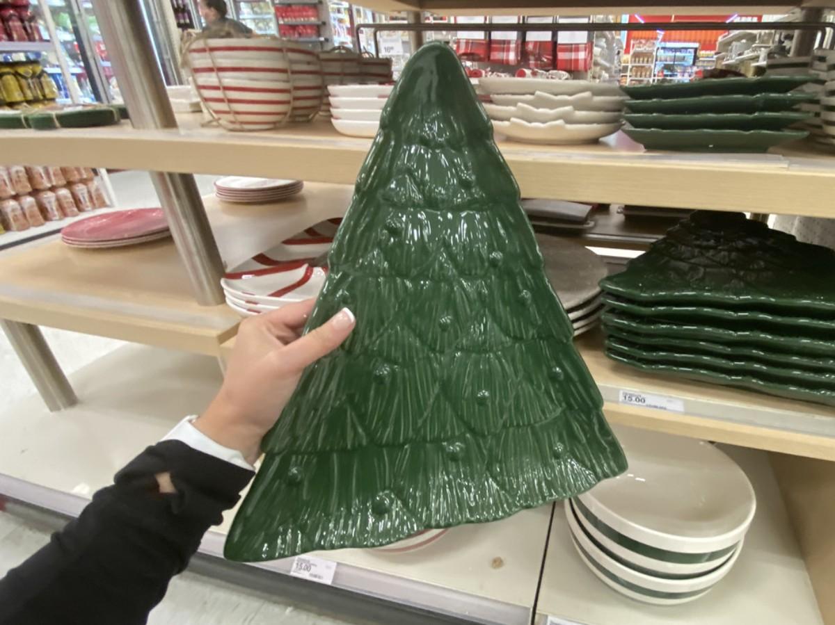 memegang nampan kue berbentuk seperti pohon natal