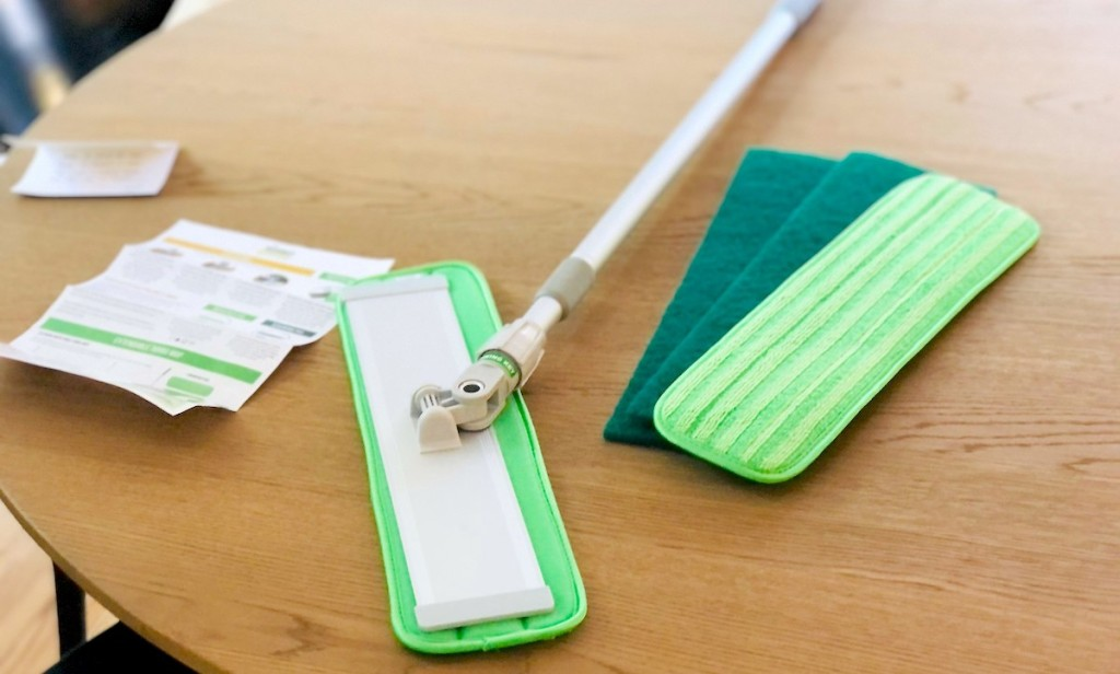 turbo mop with extra cleaning pads laying on wood table