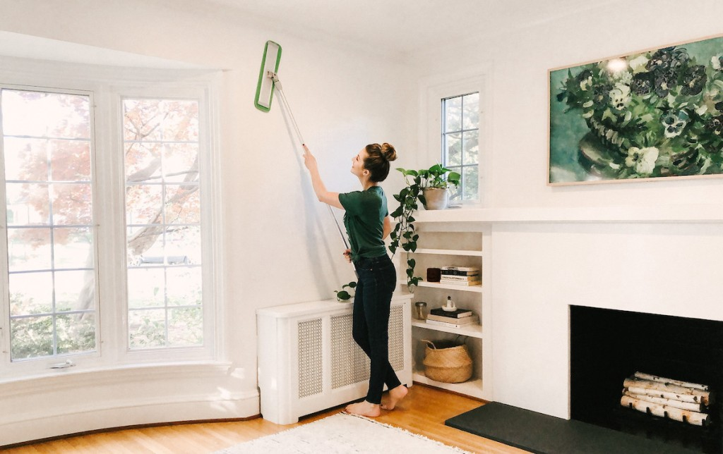 woman using turbo mop on white wall
