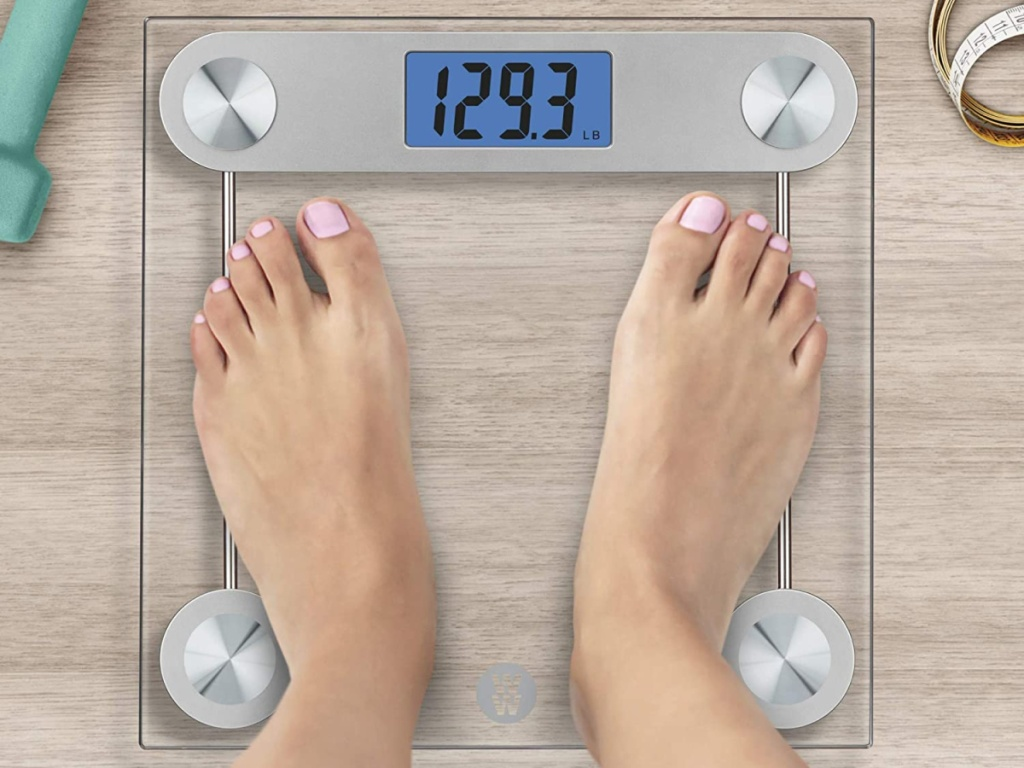 person standing on weight watchers glass scale