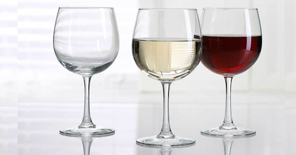 three wine glasses two with wine in them