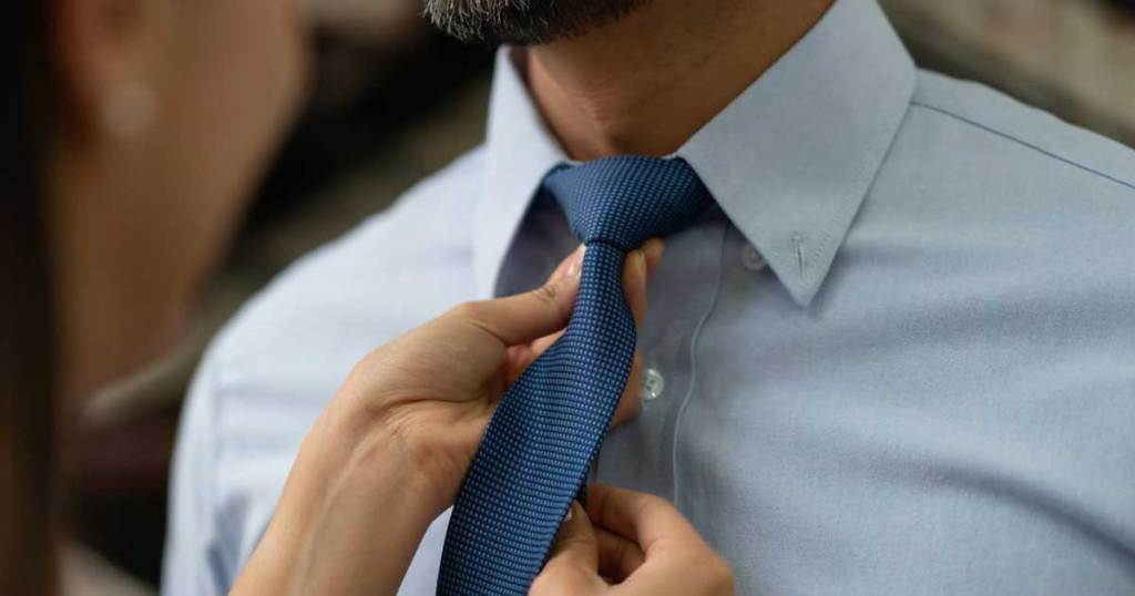 woman adjusting man's neck tie