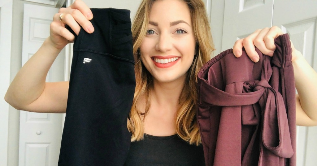 woman holding two pairs of pants
