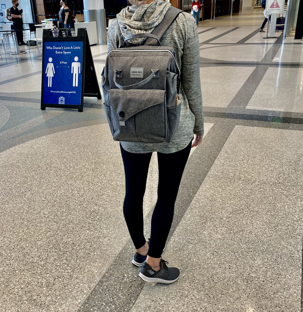 woman in the airport with travel backpack on