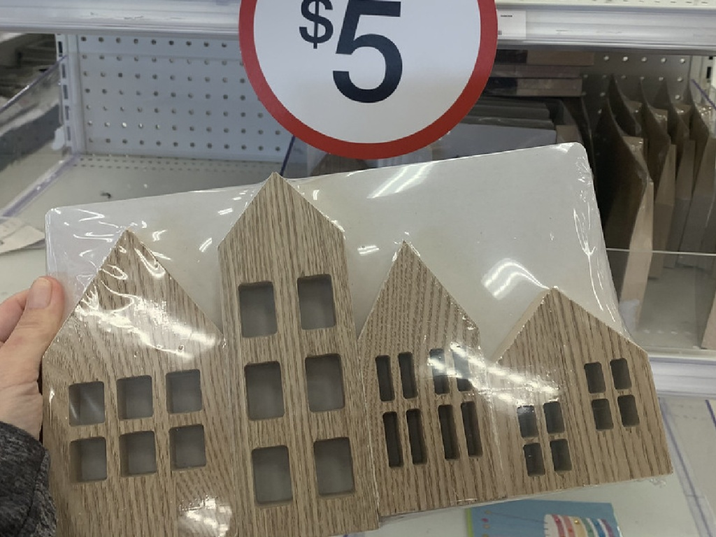 hand holding package of four wooden houses