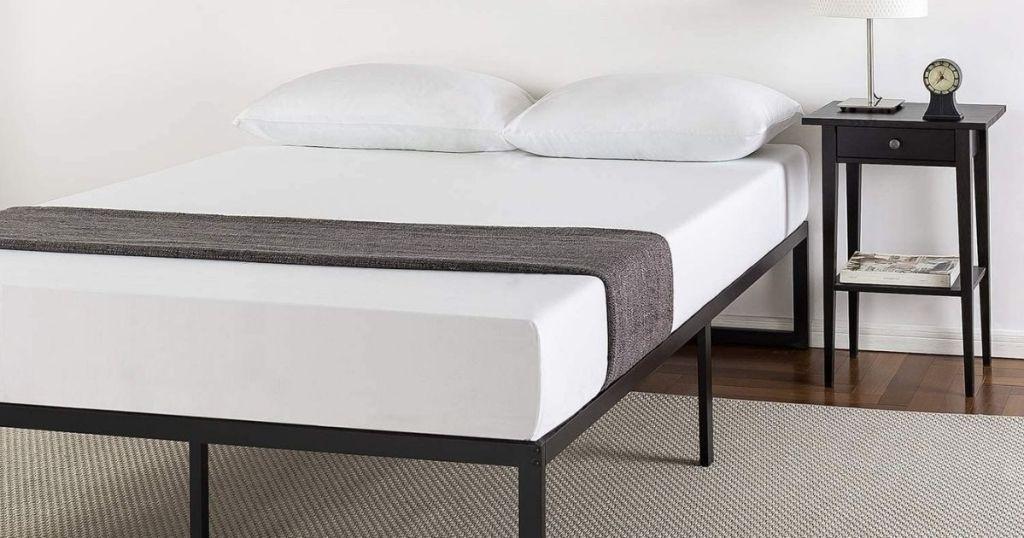 mattress on black frame in bedroom