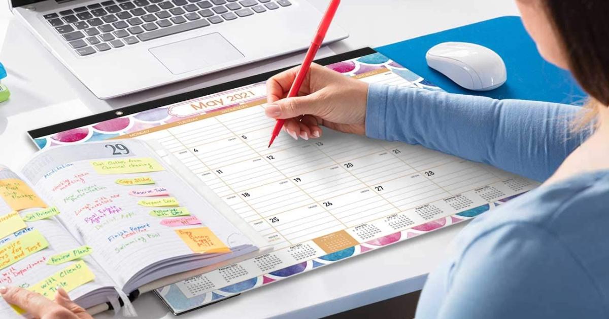 woman holding a red pen writing on a desk calendar