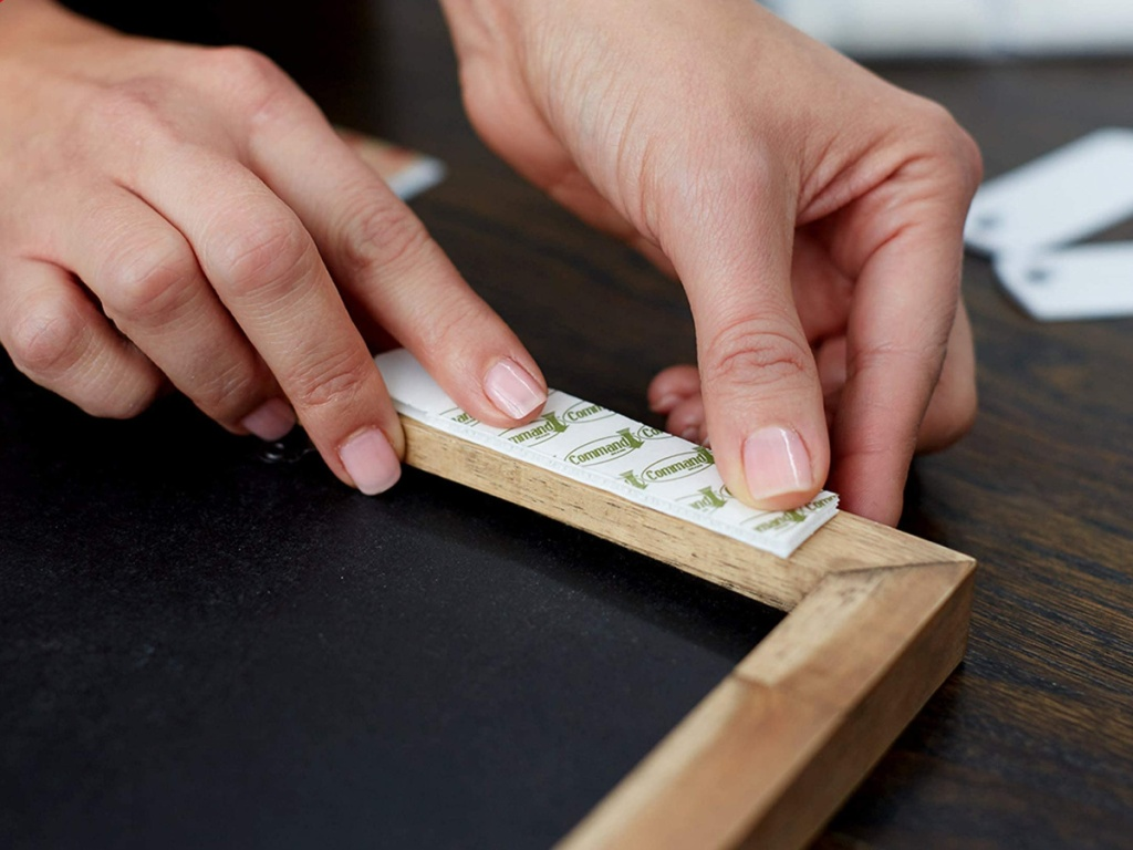 hands putting command strips on the back of a frame