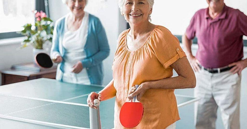 Wanita yang memegang dayung dan bola ping pong
