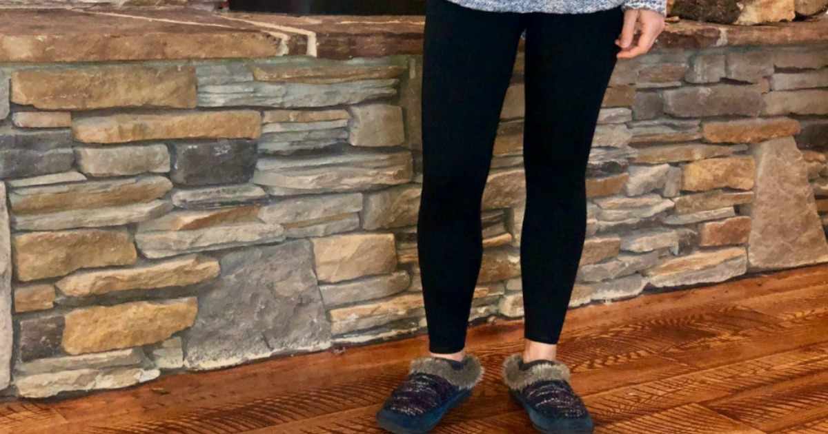 woman wearing black leggings and slippers standing in front of a slate slab wall