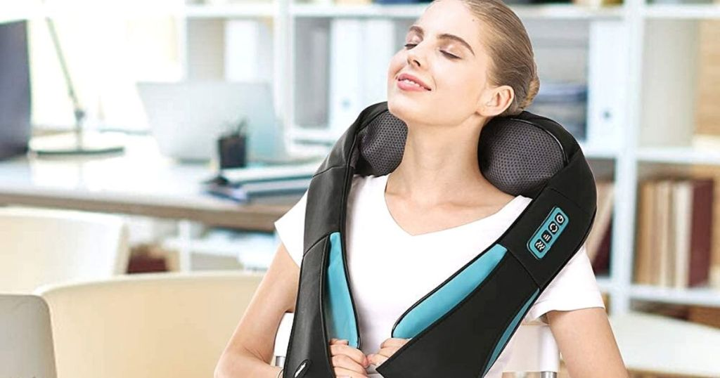 woman using neck massager at the office