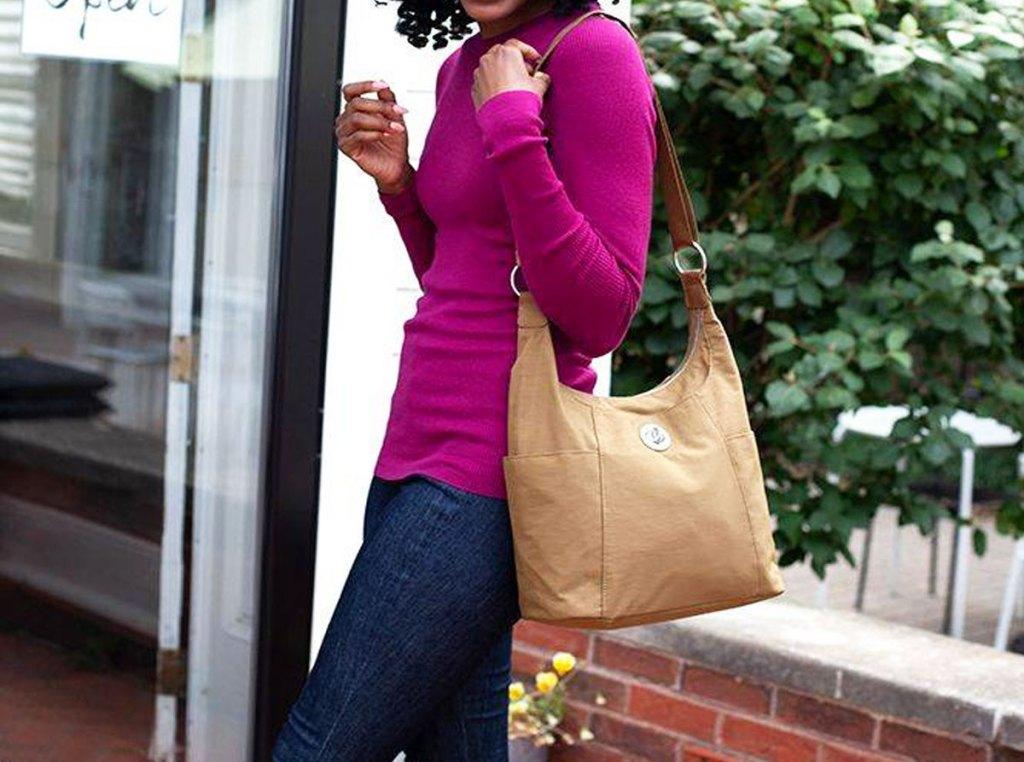 Wanita dengan sweter ungu dengan tas batak coklat di bahunya berdiri di luar ruangan