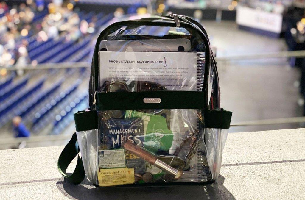 tas ransel bening berisi barang-barang yang terletak di tepi langkan yang menghadap ke stadion
