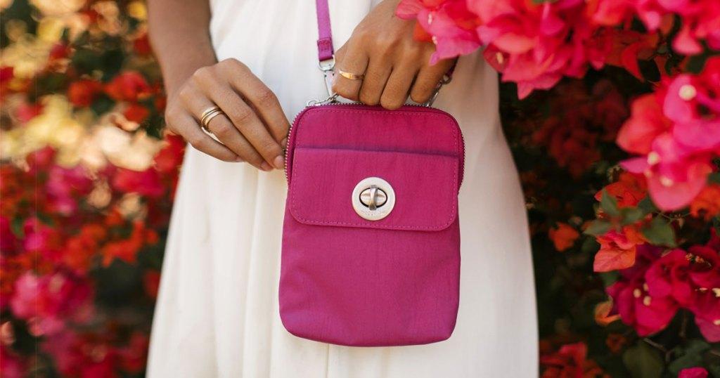 wanita dalam gaun putih dengan tas selempang merah muda cerah di sisinya